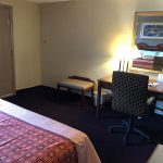 bed end across from work desk, chair, mirror, and ottoman at Travel Inn & Suites
